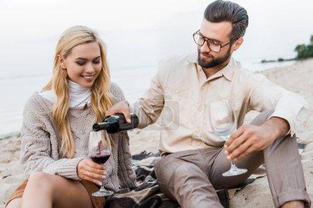 Photo pour Beau petit ami en tenue d'automne versant du vin rouge dans des verres sur la plage - image libre de droit