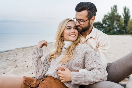smiling girlfriend and boyfriend in autumn outfit sitting and hugging on beach