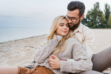 affectionate couple in autumn outfit sitting and hugging on beach