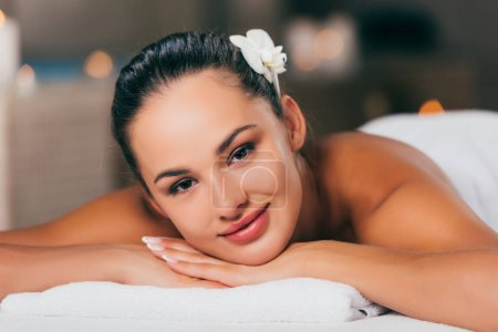 happy woman relaxing at spa salon and looking at camera