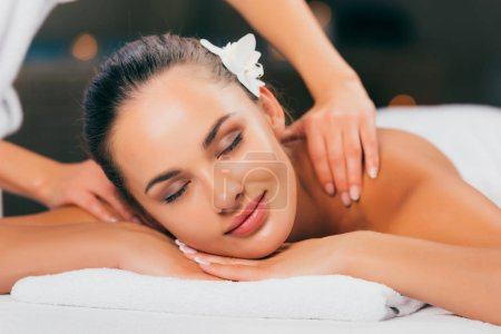 attractive young woman having massage and relaxing at massage salon