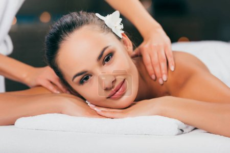 woman relaxing and having massage at spa salon and looking at camera