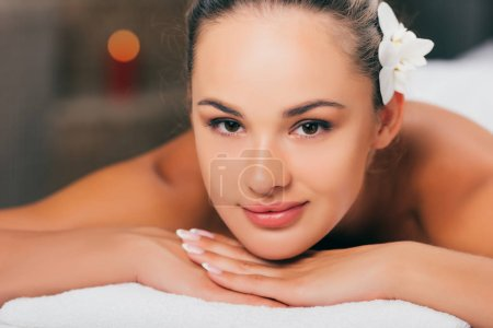 beautiful woman smiling at spa salon and looking at camera