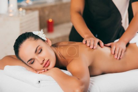 attractive woman having massage therapy at spa center
