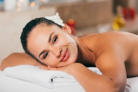 happy woman with flower in hair relaxing at spa salon and looking at camera