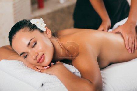 smiling woman having massage therapy at spa salon