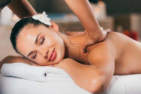 happy woman with flower in hair having massage therapy at spa salon