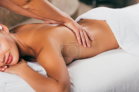 cropped view of relaxing woman having massage therapy at spa salon