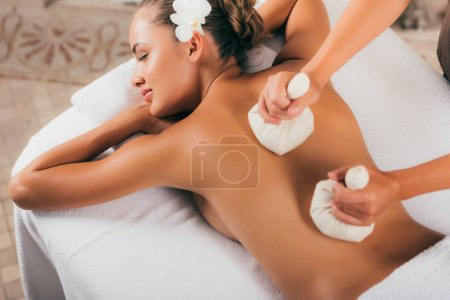 beautiful woman receiving treatment at massage salon