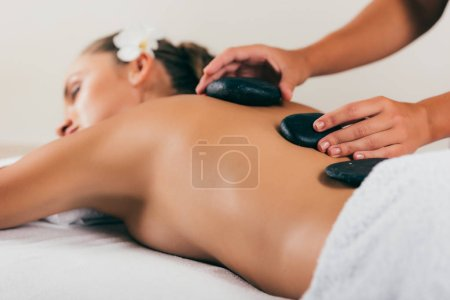 Photo for Relaxing woman having stone therapy at spa salon - Royalty Free Image