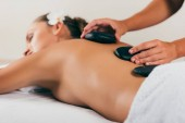 relaxing woman having stone therapy at spa salon