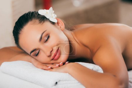 woman with white flower in her hair resting at spa salon