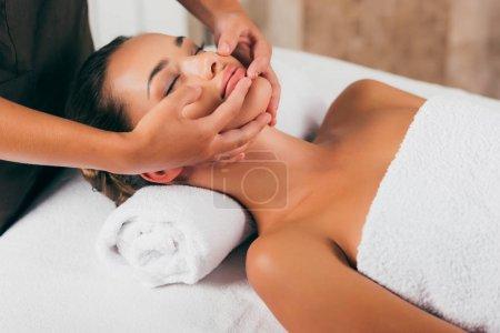 beautiful woman having face massage in spa salon