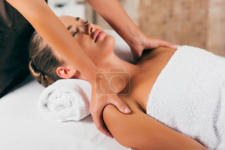 relaxing woman having massage at spa center