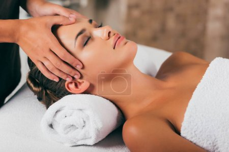 young woman relaxing and having face massage