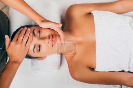 gorgeous woman relaxing and having face massage in spa salon