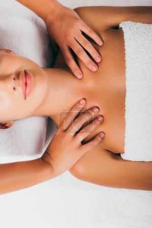 relaxing young woman having shoulders massage at spa salon