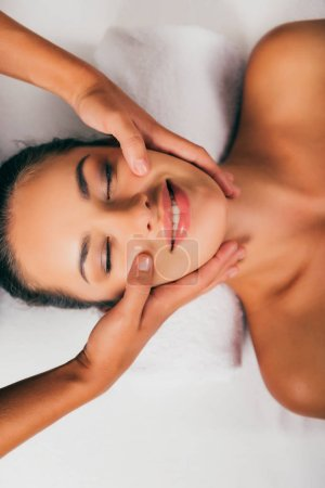 smiling woman relaxing and having face massage in spa salon