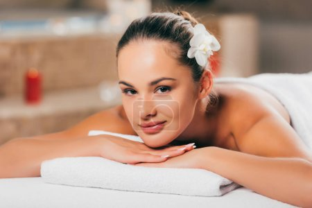 beautiful young woman relaxing at spa salon and looking at camera