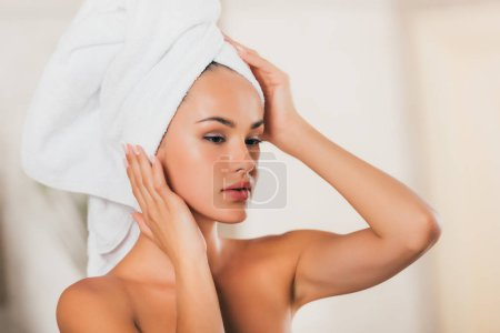 attractive young woman correcting towel on head at spa center