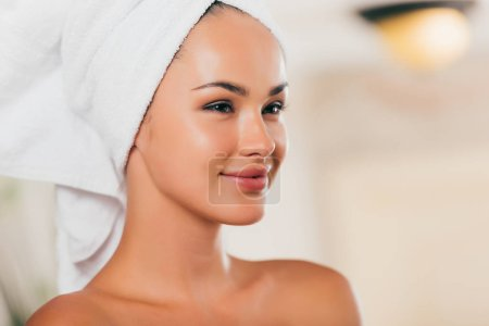 happy young woman relaxing with towel on head