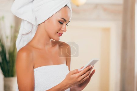 young smiling woman using smartphone at spa salon