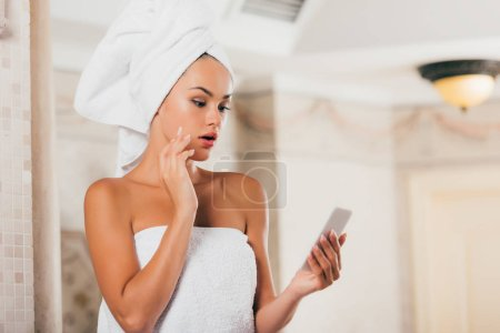 surprised woman using smartphone at spa salon