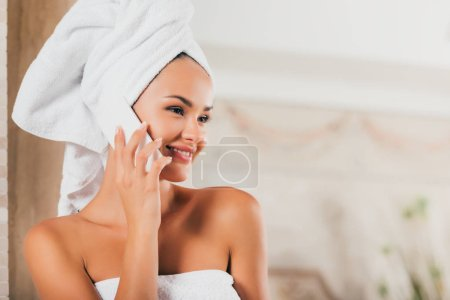smiling woman talking on smartphone at spa salon
