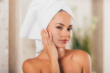 Happy woman in bath robe with clean face at spa center