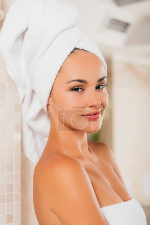 young smiling woman relaxing with towel on head