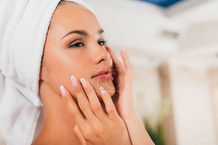 Happy woman in towel with perfect clean face at spa center