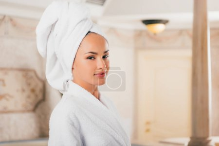 young woman in bathrobe with towel on head at spa salon