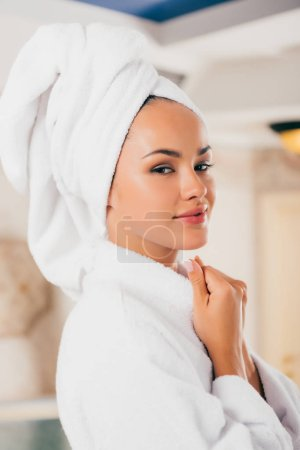 smiling woman in bathrobe with towel on head at spa salon