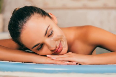 woman relaxing with closed eyes at spa salon
