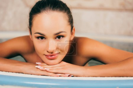 attractive woman resting in swimming pool in spa salon and looking at camera