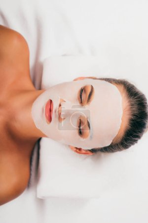 attractive young woman in mask on face relaxing with closed eyes in spa center