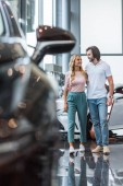 young couple choosing automobile at dealership salon