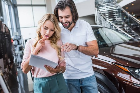 portrait of couple with catalog choosing car at dealership salon