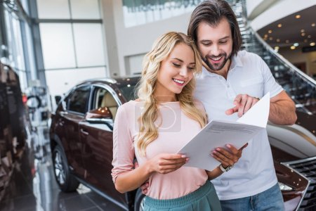 portrait of cheerful couple with catalog buying car at dealership salon