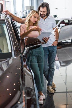 couple with catalog buying car at dealership salon
