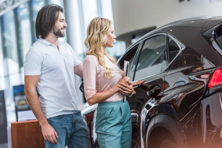 couple with catalog buying car at dealership salon