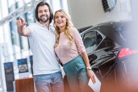 smiling couple with catalog buying car at dealership salon