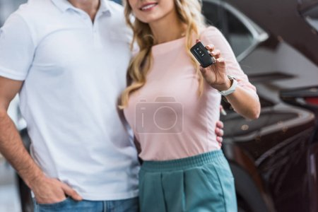partial view of couple with car key standing at dealership salon