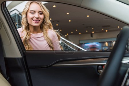 portrait of smiling woman looking into new car in dealership salon