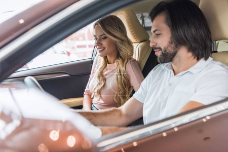 young couple sitting in new car for test drive at dealership salon