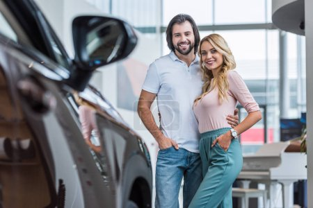 portrait of happy couple hugging at dealership salon