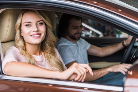 portrait of happy couple in new car at dealership salon