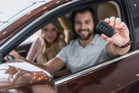 Photo for Selective focus of smiling couple with car key sitting in new car at dealership salon - Royalty Free Image