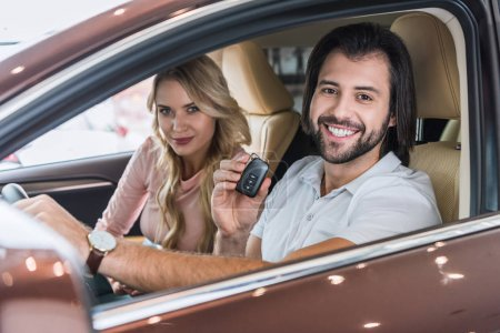 smiling couple with car key sitting in new car at dealership salon