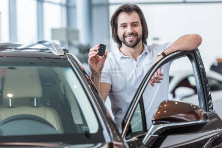 portrait of happy man with car key standing at new car in dealership salon